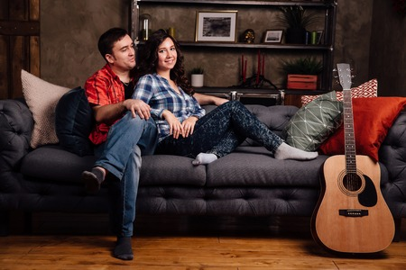 couple is sitting on the couch with a guitar. Long hair of a brunette with an acoustic guitar.