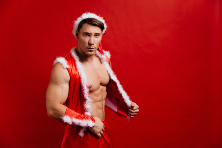 christmas holidays. sexy strong santa claus wearing hat. Young muscular man. red background.
