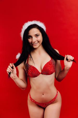 Christmas sport ans activity. Portrait of young, sexy beautiful bikini woman wears Santa hat.
