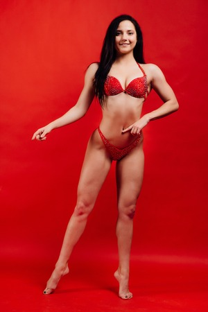 beautiful young girl fitness model stands on red background in sexy bra. Stock Photo