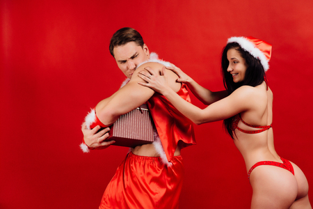 Christmas and New Years gifts, holidays. sexy Santa Claus gives a gift box to hot girl