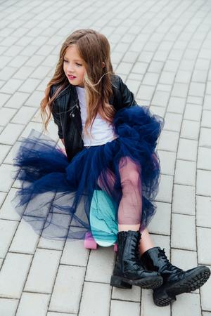 Fashion kid schoolgirlwith skateboard in the city on the street. Foto de archivo