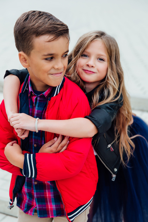 girlfriend hugs a guy from behind in the street in the city. Two children together embrace.