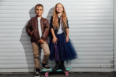 Portrait of two teenage school children on a garage door background in a city park street.