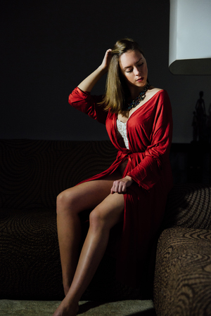 Beautiful sexy lady in elegant red robe. Fashion portrait of model indoors.