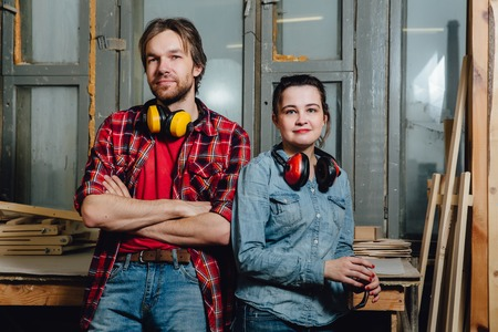 Portrait of carpenters in the workshop. A man and a girl, leaned back and posed. Stock Photo