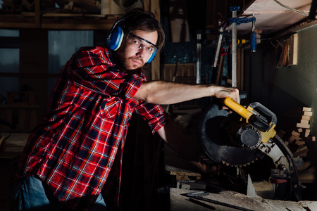 brunette man profession carpenter builder saws with a circular saw a wooden board.