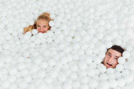 couple of loving friends have fun surrounded by white plastic balls in a dry swimming pool.