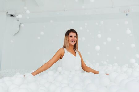 Portrait Happy woman stand surrounded by white plastic balls in the dry pool. Copy splace.