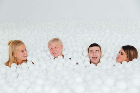 Happy Friendly family surrounded by white plastic balls in the dry pool.