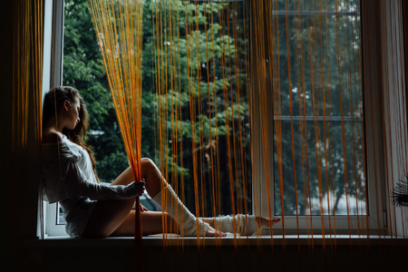 Young beautiful girl is sitting on the windowsill. Orange curtains. Long curly hair.