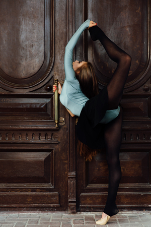 Graceful beautiful girl ballerina posing on the street of the vintage theater wood door. Stock Photo