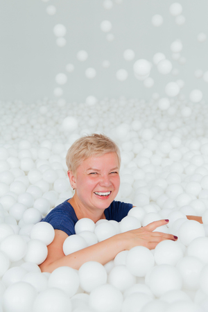Portrait of beautiful senior woman with white short hair surrounded by white plastic balls.