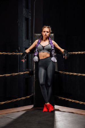 Sexy boxing girl stands leaned on ropes of competition ring.