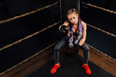 Boxing fashion girl on break sits on a chair resting in a boxing competition ring.