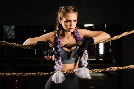 Sexy boxing girl leaned kneels on ropes of competition ring. Fashionable portrait.