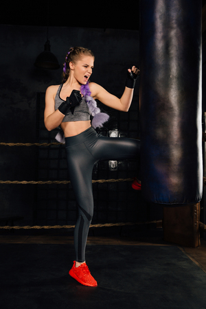 Young woman trains in boxing ring with heavy punching bag. Stock Photo