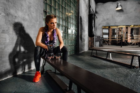 Fitness girl relaxing sitting on sports school bench after a hard boxing training. Stock Photo