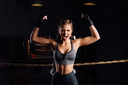 Young fashion boxer girl with boxing gloves screams emotionally rising arms.