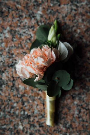 boutonniere, button hole flower, a cream peonies on granite table.