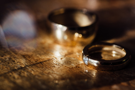 Two beautiful golden wedding rings and earrings on a wooden background. 免版税图像