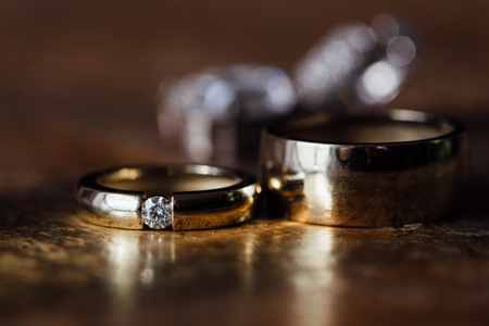 Two beautiful golden wedding rings and earrings on a wooden background. Stock Photo