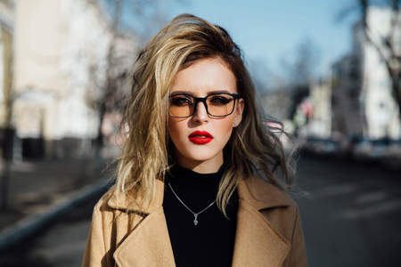 Fashion young girl in glasses. Blonde, red lips, beige coat walking along the city street. 스톡 콘텐츠