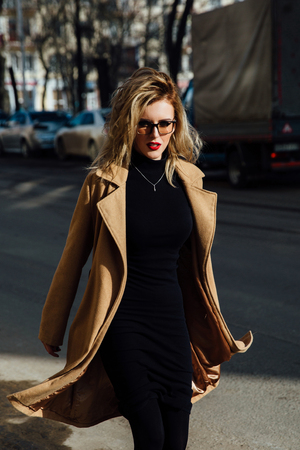 A fashionable blonde young girl in glasses wearing a beige coat walking along the city street.