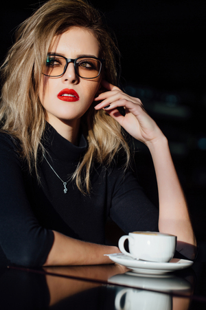 A beautiful fashionable stylish girl sits in a cafe with a cup of coffee.