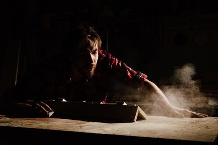 carpenter blows off wood dust cloud.