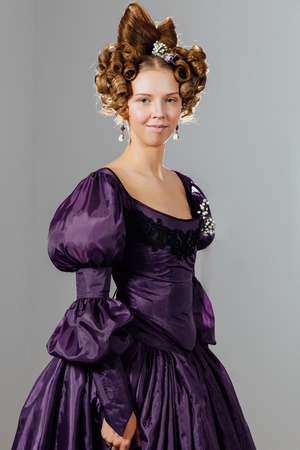 Beautiful young woman in vintage dress with designer hair. Ball, evening reception.