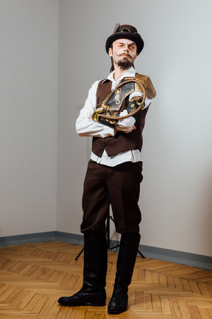 Portrait of steampunk vintage man with various mechanical devices on body.