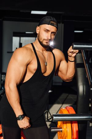 Big strong man fitness model resting in the gym. leaned against the simulator sport equipment.