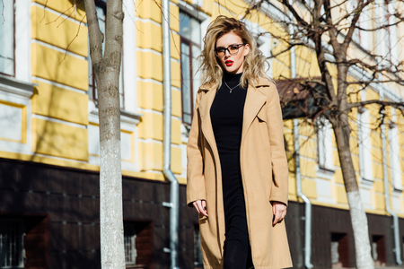Fashion young girl in glasses. Blonde, red lips, beige coat walking along the city street. Stock Photo