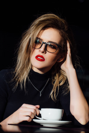 Beautiful fashionable stylish girl sits in a cafe with a cup of coffee. Stock Photo