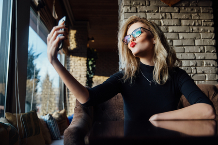 Young beautiful blonde woman taking a selfie in coffee shop. Hipster, red lips, glasses. Stock Photo