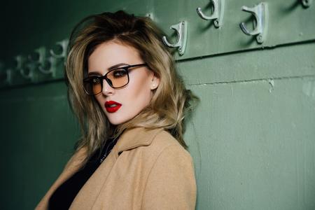 Trendy Hipster Girl in glasses on vintage dressing room background.