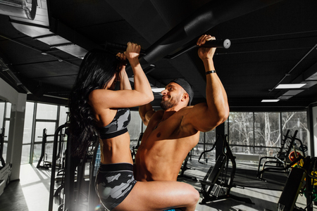 Fitness couple pulling themselves up in the gym together embracing.