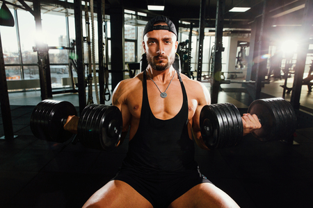 Fitness model of a strong man sitting on a bench trains with dumbbells.