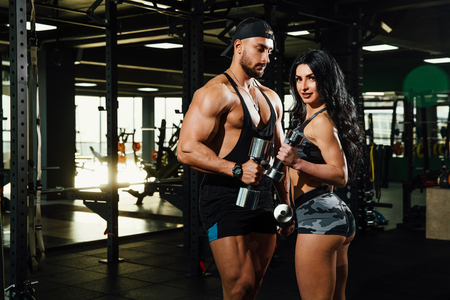 Portrait of fit sportive couple posing with dumbbells looking at camera in modern gym. Stock Photo