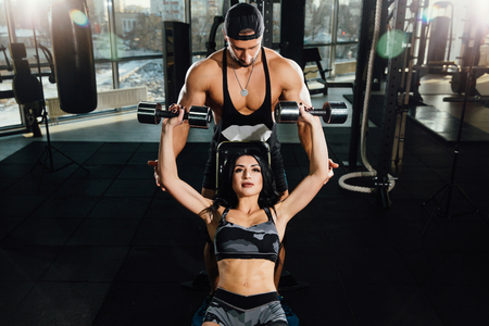 Sporty girl doing weight dumbbells exercises with assistance of her personal trainer at public gym.