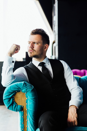 Stylish athletic man in a business costume vest. Sits in the turquoise sofa chair, a serious look.