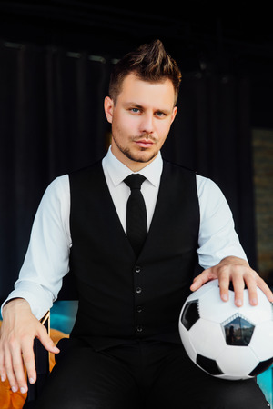 Stylish athletic man in a business suit and a soccer ball. Against the background of a loft wall.