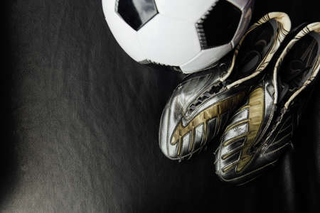 Flat lay soccer football accessories on a dark leather background. Mock-up with copy space for text.