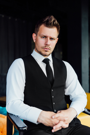 Stylish athletic man in a business costume vest. Sits in the directors chair, a serious look.