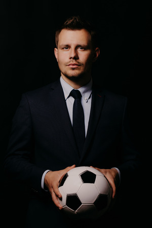 young handsome businessman holding a football on black background studio.