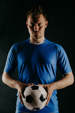 Young soccer player with ball on black background in studio.