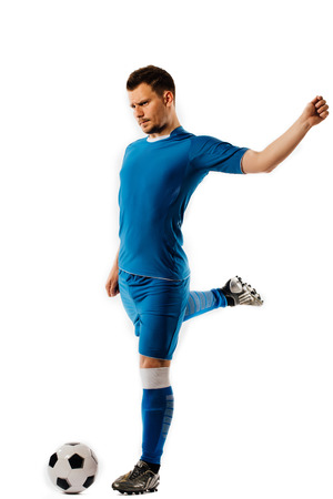 Young handsome football player holds kicking soccer ball posing on white isolated background.