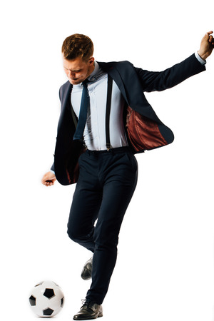young handsome businessman manager kicking a soccer ball on white background isolated.