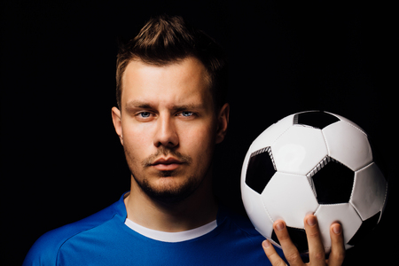 Close-up portrait of young handsome football player soccer posing on dark background.